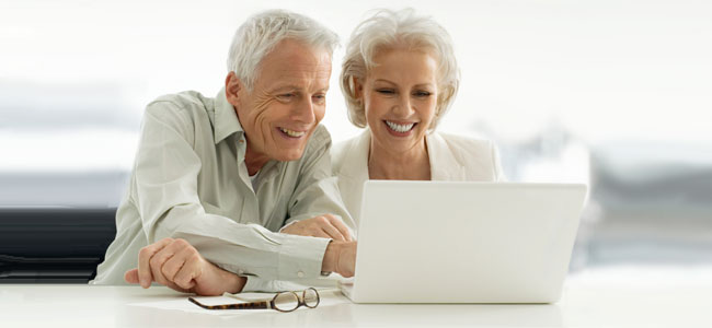 older couple looking at laptop with papers beside them
